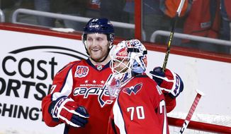 Washington Capitals defenseman Karl Alzner (27) and goalie Braden Holtby (70) celebrate after an NHL hockey game against the Ottawa Senators, Monday, Dec. 22, 2014, in Washington. The Capitals won 2-1. (AP Photo/Alex Brandon)