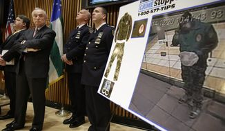 New York City Police Commissioner Bill Bratton, second from left, looks at a video frame of Ismaaiyl Brinsley during a news conference at police headquarters in New York, Monday, Dec. 22, 2014. Police are asking for the public's help in identifying his whereabouts before he killed two police officers and himself on Saturday afternoon. (AP Photo/Seth Wenig)