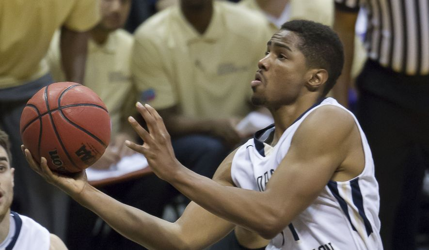 George Washington guard Kethan Savage shoots over Ohio forward Treg Setty, bottom, but is called for a charging foul in the second half of an NCAA college basketball game at the Diamond Head Classic on Monday, Dec. 22, 2014, in Honolulu. George Washington won 77-49. (AP Photo/Eugene Tanner)