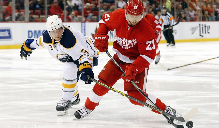 Buffalo Sabres defenseman Mark Pysyk (3) knocks the puck from Detroit Red Wings left wing Tomas Tatar (21) in the second period during an NHL hockey game in Detroit, Tuesday, Dec. 23, 2014. (AP Photo/Paul Sancya)
