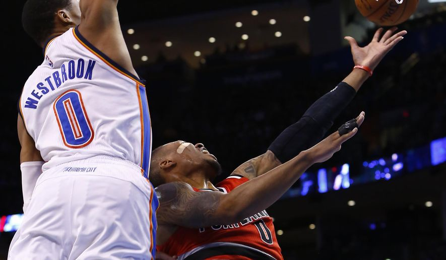 Portland Trail Blazers guard Damian Lillard, right, goes to the basket in front of Oklahoma City Thunder guard Russell Westbrook, left, during the second quarter of a NBA basketball game in Oklahoma City, Tuesday, Dec. 23, 2014. (AP Photo/Alonzo Adams)