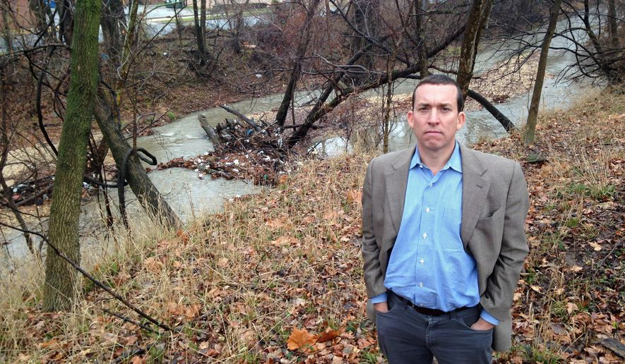 This photo taken Dec. 16, 2014 shows  BrightFarms Inc. CEO Paul Lightfoot standing near the banks of the Oxon Run in Washington, on land that his company is leasing from the District of Columbia government to build a greenhouse and urban farm. Lightfoot is considering abandoning the project because of extensive contamination on the city-controlled land, which has been used for years for illegal dumping and an unlicensed landfill. Some of the waste has made it into the waterway, a tributary of the Potomac River. (AP Photo/Ben Nuckols)