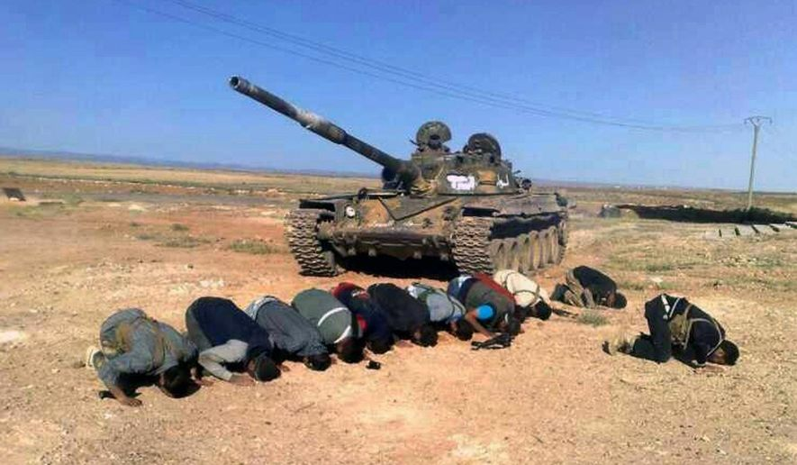 In this April 30, 2014, file image provided by the Syrian Revolution Against Bashar Assad, which has been authenticated based on its contents and other AP reporting, Syrian rebels pray in front of their tank at al Mutayia village in the southern province of Daraa, Syria. (AP Photo/the Syrian Revolution Against Bashar Assad, File)