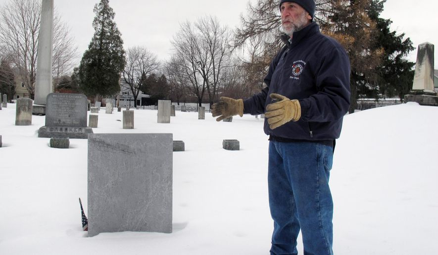 In this Thursday, Dec. 18, 2014 photo, Art Cohn of the Lake Champlain Maritime Museum stands in front of the grave of War of 1812 hero Joseph Barron Jr., in Burlington, Vt. Cohn says an early 20th century debate about Barron's final resting place was settled in 1906 when the Burlington grave was dug up and the remains proved to be those of Barron. The American victory in the 1814 Battle of Plattsburgh, in which Barron was killed, helped lead to the end of the War of 1812, signed 200 years ago in Ghent, Belgium. (AP Photo/Wilson Ring)