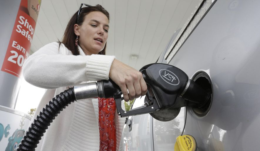 FILE - In this Nov. 12, 2014 file photo, Lydia Holland fills up at a gas station in Sacramento, Calif. In the second half of 2014, the price of oil dropped by half, to depths not seen since May of 2009 when the U.S. was in the Great Recession. By December, some drivers even saw a price at the pump that started with a $1. (AP Photo/Rich Pedroncelli, File)