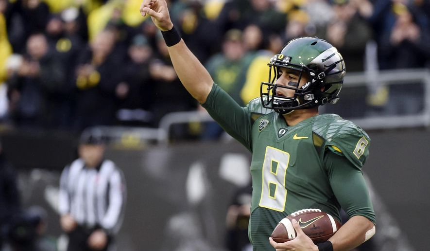 FILE - In this Nov. 22, 2014, file photo, Oregon quarterback Marcus Mariota (8) celebrates after scoring a touchdown during the first quarter of an NCAA college football game against the Colorado in Eugene, Ore. Mariota is The Associated Press college football player of the year. He won the AP vote in the same landslide fashion he won the Heisman Trophy, receiving 49 of the 54 votes submitted by the AP Top 25 media panel. (AP Photo/Steve Dykes, File0