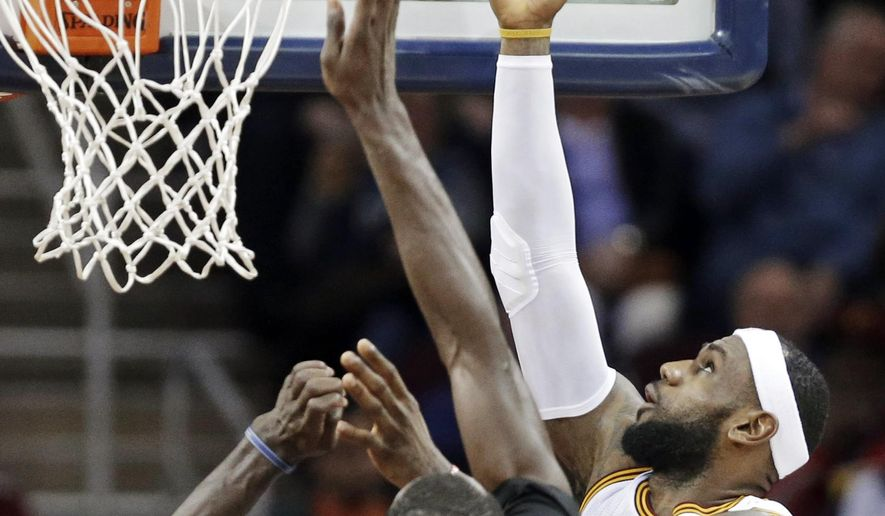 Cleveland Cavaliers' LeBron James lays in a shot over Minnesota Timberwolves' Gorgui Dieng (5) during the second quarter of an NBA basketball game Tuesday, Dec. 23, 2014, in Cleveland. (AP Photo/Mark Duncan)