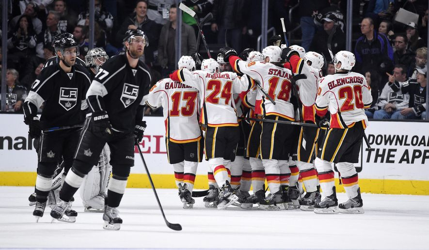 Members of the Calgary Flames, right, celebrate as member of the Los Angeles Kings skate off the ice after Flames' defenseman Mark Giordano scored a game-winning goal during the third period of an NHL hockey game, Monday, Dec. 22, 2014, in Los Angeles.  The Flames won 4-3 in overtime. (AP Photo/Mark J. Terrill)