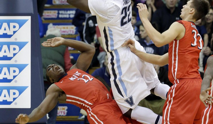 Villanova's JayVaughn Pinkston, center, shots against New Jersey Institute of Technology's Odera Nweke, left, and Vlad Shustov, of Russia, during the first half of an NCAA college basketball game, Tuesday, Dec. 23, 2014, in Villanova, Pa. (AP Photo/Matt Slocum)