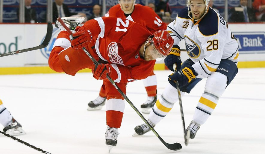 Detroit Red Wings left wing Tomas Tatar (21) tries to shoot as Buffalo Sabres center Zemgus Girgensons (28) defends in the second period during an NHL hockey game in Detroit Tuesday, Dec. 23, 2014. (AP Photo/Paul Sancya)