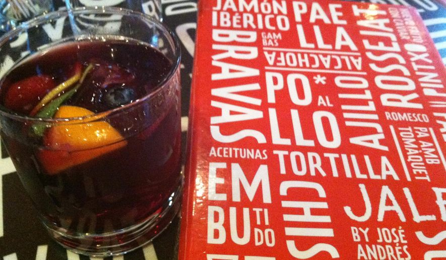 This Oct. 23, 2014 photo shows a glass of sangria next to a menu at the Jaleo restaurant in Bethesda, Maryland. The tapas menu by chef Jose Andres offers numerous choices of flavorful small plates inspired by Spanish cuisine, made with simple but authentic ingredients. (AP Photo/Beth J. Harpaz)