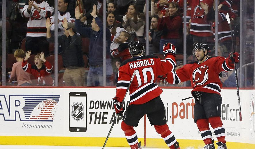 New Jersey Devils right wing Stephen Gionta, right, celebrates with Peter Harrold (10) after scoring a goal against the Carolina Hurricanes during the first period of an NHL hockey game, Tuesday, Dec. 23, 2014, in Newark, N.J. (AP Photo/Julio Cortez)
