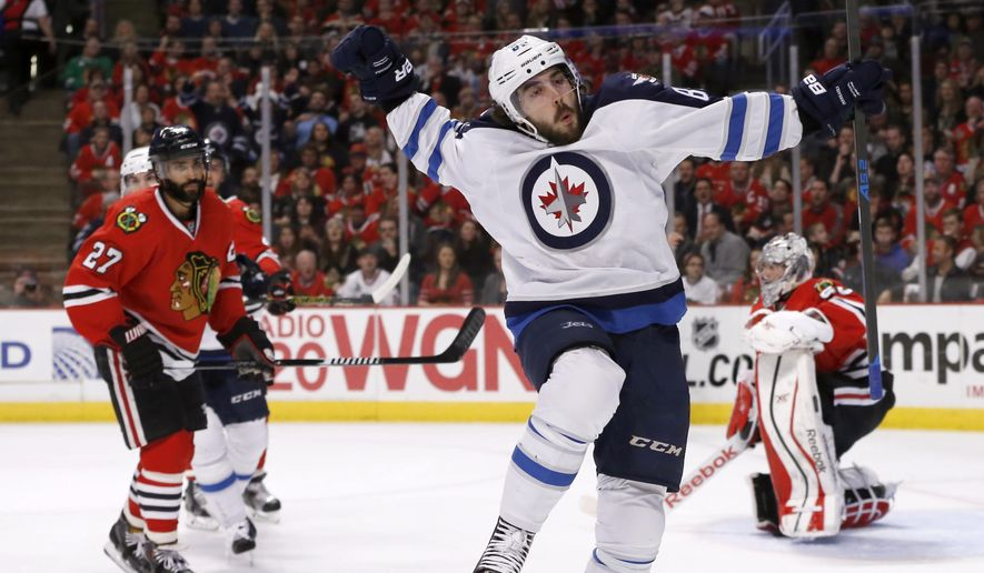 Winnipeg Jets center Mathieu Perreault, center, celebrates after scoring on Chicago Blackhawks goalie Corey Crawford, right, as defenseman Johnny Oduya (27) watches, during the first period of an NHL hockey game Tuesday, Dec. 23, 2014, in Chicago. (AP Photo/Charles Rex Arbogast)