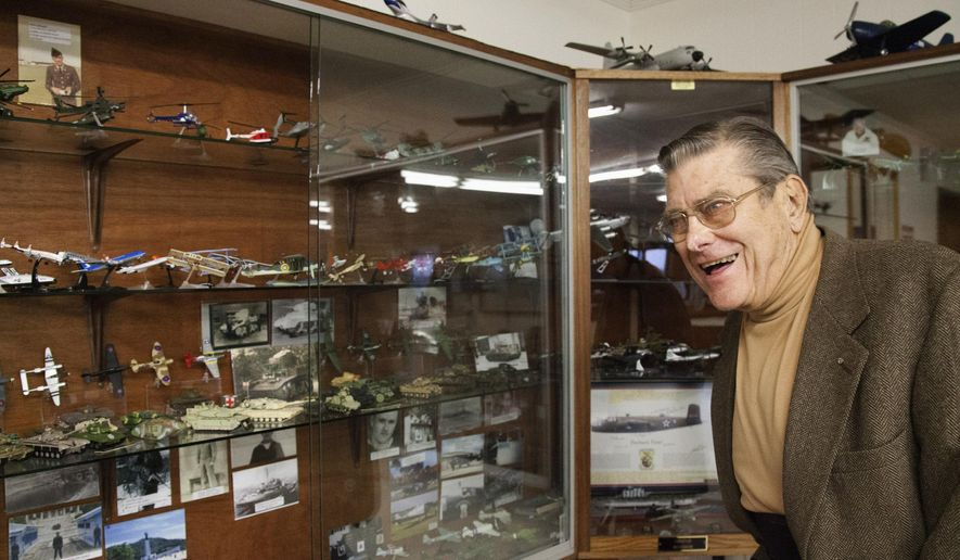 In this Nov. 24, 2014 photo, John McClure shows off his massive model plane and tank collection, which he has been adding to for 25 years, that is on display at the Taylorville Municipal Airport in Taylorville, Ill. (AP Photo/Herald & Review, Hugh Sullivan)