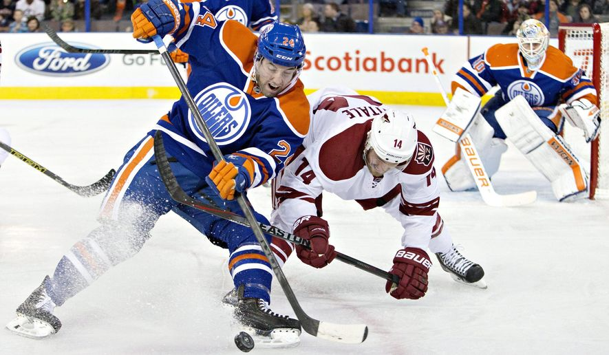 Arizona Coyotes' Joe Vitale (14) and Edmonton Oilers' Brad Hunt (24) battle for the puck as goalie Ben Scrivens (30) looks on during the first period of an NHL hockey game in Edmonton, Alberta, Tuesday, Dec. 23, 2014. (AP Photo/The Canadian Press, Jason Franson)