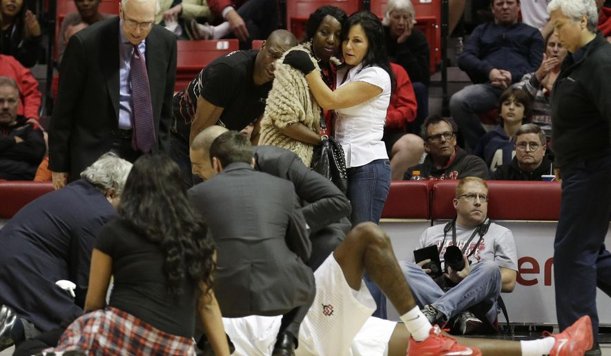 San Diego State forward Dwayne Polee II lies prone on the court as his mother Yolanda Polee, above in yellow sweater, looks on with Polee's father, Dwayne Polee, in black shirt, and an unidentified woman while playing UC Riverside during the first half of an NCAA college basketball game Monday, Dec. 22, 2014, in San Diego. Polee was conscious as he was carried off the court on a stretcher by paramedics. (AP Photo/Gregory Bull)