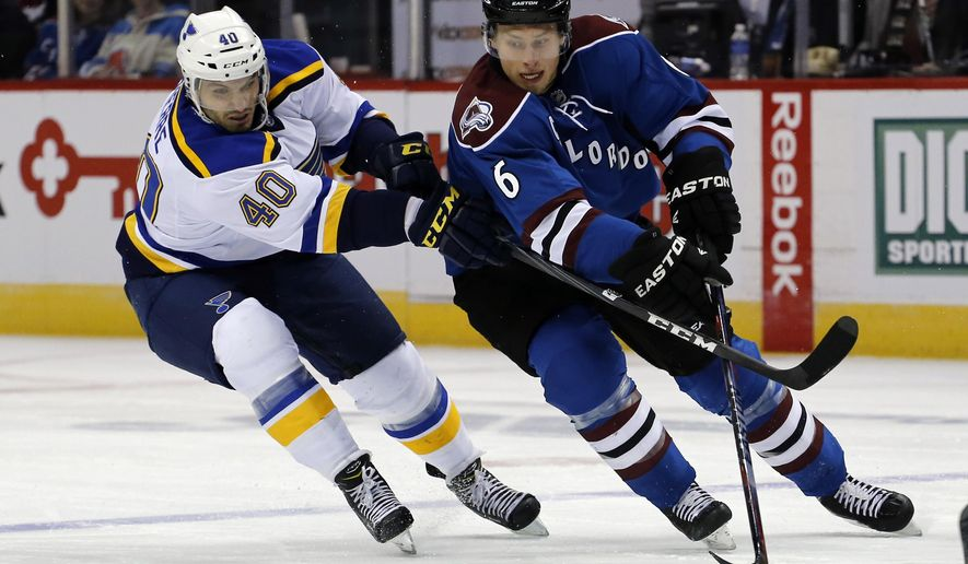 St. Louis Blues center Maxim Lapierre (40) and Colorado Avalanche defenseman Erik Johnson (6) go after the puck during the first period of an NHL hockey game Tuesday, Dec. 23, 2014, in Denver. (AP Photo/Jack Dempsey)