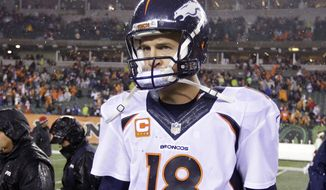 Denver Broncos quarterback Peyton Manning (18) walks off the field following an NFL football game against the Denver Broncos Monday, Dec. 22, 2014, in Cincinnati. Cincinnati won 37-28. (AP Photo/Michael Conroy)