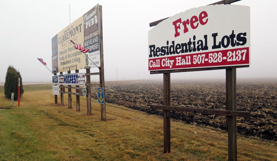 In this Dec. 14, 2014 photo, signs advertising free residential lots are seen in Claremont, Minn. A small southeastern Minnesota community is trying but failing to give away land for free. Claremont, which has about 500 residents, has had no takers in the three years it has been offering free lots to anyone with a qualifying income who is willing to build a house, Minnesota Public Radio News reported. (AP Photo/Minnesota Public Radio, Elizabeth Baier)
