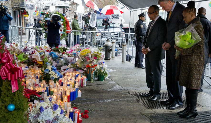 From left, Pastor Michael Durso, New York City Mayor Bill de Blasio and New York City first lady Chirlane McCray visit a makeshift memorial Tuesday, Dec. 23, 2014, near the site where New York Police Department officers Rafael Ramos and Wenjian Liu were shot and killed in the Brooklyn borough of New York. Police say Ismaaiyl Brinsley ambushed the two officers in their patrol car in broad daylight Saturday, fatally shooting them before killing himself inside a subway station. (AP Photo/Craig Ruttle)