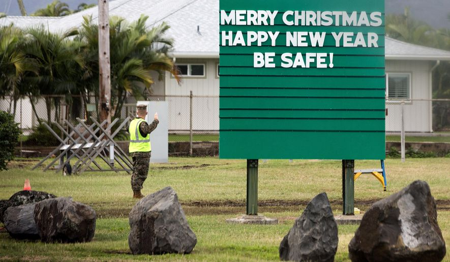 "A sign that reads ""Merry Christmas, Happy New Year, Be Safe!,"" and a Marine are seen from the motorcade carrying President Barack Obama from Marine Corps Base Hawaii after he went to the gym, Tuesday, Dec. 23, 2014, in Kailua, Hawaii, during the Obama family vacation. (AP Photo/Jacquelyn Martin)"