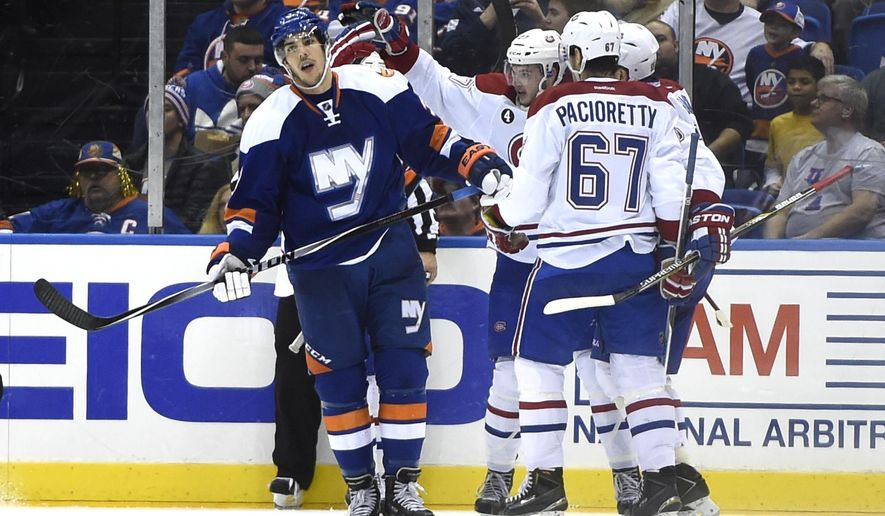 Montreal Canadiens left wing Max Pacioretty (67), center Alex Galchenyuk (27) and teammates celebrate right wing Brendan Gallagher's goal as New York Islanders defenseman Travis Hamonic (3) skates past during the first second period of an NHL hockey game at Nassau Coliseum on Tuesday, Dec. 23, 2014, in Uniondale, N.Y. (AP Photo/Kathy Kmonicek)