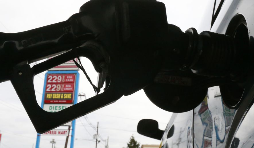 FILE - In this Dec. 18, 2014 file photo, gas is pumped into a car at the Eastcoast filling station in Pennsauken N.J.  In the second half of 2014, the price of oil dropped by half, to depths not seen since May of 2009 when the U.S. was in the Great Recession. By December, some drivers even saw a price at the pump that started with a $1.  (AP Photo/Matt Rourke, File)
