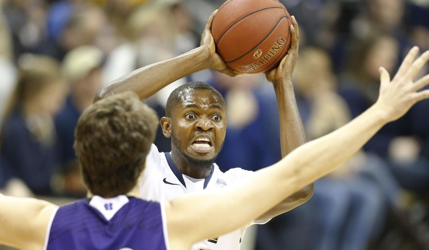 Pittsburgh's Joseph Uchebo, right, looks to pass as Holy Cross's Matt Husek defends in the first half of an NCAA college basketball game, Tuesday, Dec. 23, 2014, in Pittsburgh. (AP Photo/Keith Srakocic)