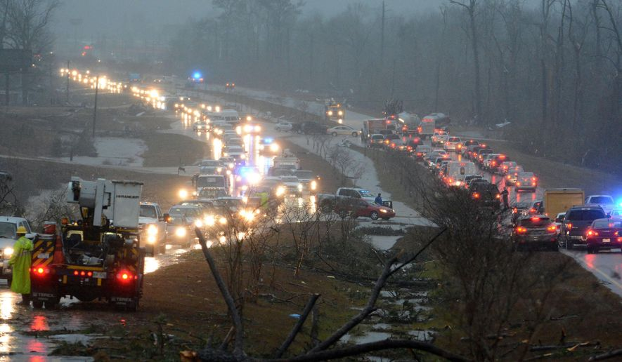 Traffic is blocked on US 98 East near Columbia, Miss., after a tornado touched down around 2:30 p.m., Tuesday, Dec. 23, 2014. Gov. Phil Bryant declared an emergency for two southeastern counties where officials say four people died in the storms and several more were injured. His office said thousands were without power Tuesday night around Columbia, which is about 80 miles southeast of Jackson. (AP Photo/The Hattiesburg American, Eli Baylis)