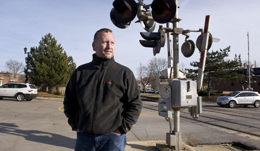 Ed Suarez stands near a railroad crossing, Tuesday, Dec. 23, 2014 in Western Springs, Ill., where he  pulled an elderly woman from her vehicle before it was struck by a Metra train Monday evening. Suarez ran from his own car when he saw the woman's vehicle turn onto the tracks and continue to drive. She told him she could not walk, so he grabbed her arm, threw it over his neck and carried her to safety. The woman was taken to a hospital in La Grange and later released.(AP Photo/Sun-Times Media, Richard A. Chapman) MANDATORY CREDIT, MAGS OUT, NO SALES