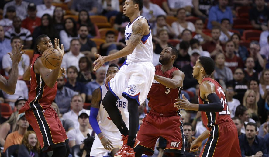 Philadelphia 76ers guard K.J. McDaniels, second from left, passes the ball past Miami Heat center Hassan Whiteside, left, during the first half of an NBA basketball game, Tuesday, Dec. 23, 2014,  in Miami. (AP Photo/Lynne Sladky)