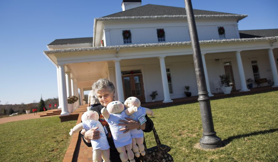 """In this Nov. 21, 2014 photo, collector Dianne Adcock, of Senoia, Ga., carries out three Cabbage Patch Kids from circa 1980, after they received a bath at Babyland General Hospital, the birthplace of Cabbage Patch Kids, in Cleveland, Ga. Adcock routinely brings in her babies for a cleaning at """"bath camp"""" in which they are cleaned and their cheeks receive a fresh tinting of rosiness. (AP Photo/David Goldman)"""