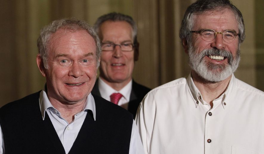 Sinn Fein President Gerry Adams, right, and party members Deputy First Minister of Northern Ireland Martin McGuinness left, Gerry Kelly, centre, smile during a press conference at Parliament Buildings, Stormont, Tuesday, Dec. 23, 2014. All-party talks involving the five main political parties in Northern Ireland reached agreement  Tuesday after 11 weeks of political talks. (AP Photo/Peter Morrison)