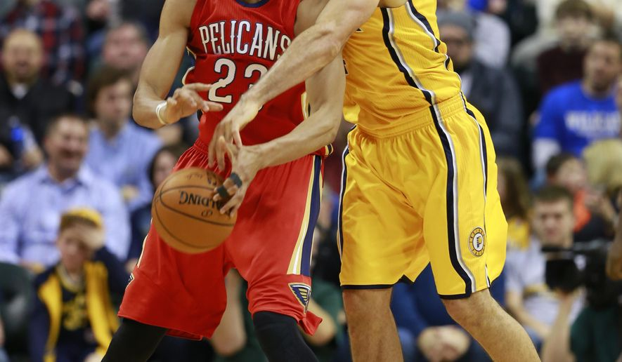 Indiana Pacers forward Luis Scola, right, knocks the basketball out of the hands of New Orleans Pelicans forward  Anthony Davis in the first half of an NBA basketball game in Indianapolis, Tuesday, Dec. 23, 2014. Indiana won 96-84.  (AP Photo/R Brent Smith)
