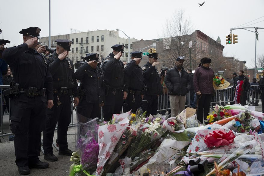 Mourners visit a makeshift memorial near the site where New York Police Department officers Rafael Ramos and Wenjian Liu were murdered in the Brooklyn borough of New York, Monday, Dec. 22, 2014. Police say Ismaaiyl Brinsley ambushed the two officers in their patrol car in broad daylight Saturday, fatally shooting them before killing himself inside a subway station.  (AP Photo/John Minchillo)