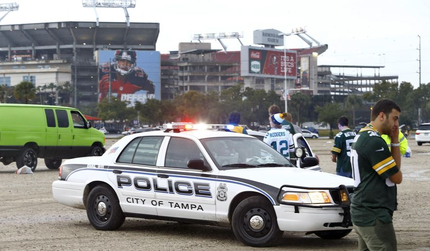 Tampa Police Officers talk to spectators after football fans were reportedly taken to the hospital with injuries after a lightning strike near the Raymond James Stadium, Sunday, Dec. 21, 2014, in Tampa, Fla. (AP Photo/Brian Blanco)