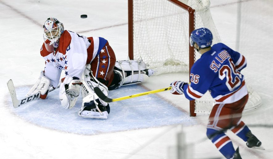 Washington Capitals goalie Braden Holtby (70) and New York Rangers' Martin St. Louis (26) watch a puck shot near the goal during the third period of an NHL hockey game Tuesday, Dec. 23, 2014, in New York. St. Louis scored on the play. The Rangers won the game 4-2. (AP Photo/Frank Franklin II)