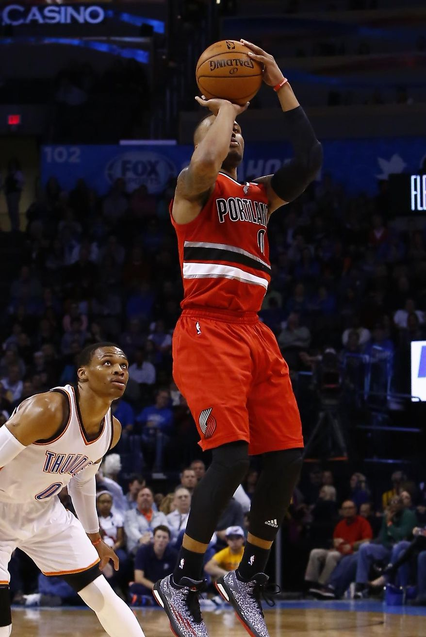 Portland Trail Blazers guard Damian Lillard (0) shoots in front of Oklahoma City Thunder guard Russell Westbrook (0) during the second quarter of a NBA basketball game in Oklahoma City, Tuesday, Dec. 23, 2014. (AP Photo/Alonzo Adams)
