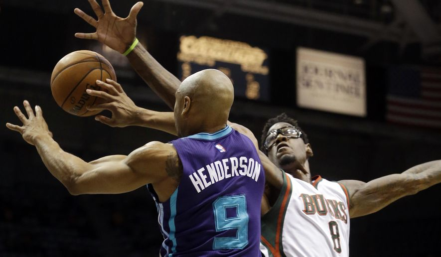 Milwaukee Bucks' Larry Sanders (8) knocks the ball away from Charlotte Hornets' Gerald Henderson during the first half of an NBA basketball game Tuesday, Dec. 23, 2014, in Milwaukee. (AP Photo/Morry Gash)