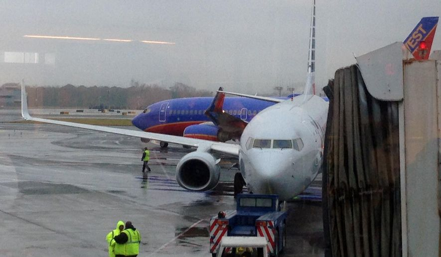 In this photo taken through a window and provided by Jenny Kao, a Southwest Airlines plane, rear, and an American Airlines plane sit on the tarmac after a wingtip on the Southwest plane was ripped off when the aircrafts collided at La Guardia Airport in New York, Tuesday, Dec. 23, 2014. The incident occurred as the arriving American Airlines Flight 1104 from Dallas was taxiing to its gate just as Southwest Airlines Flight 449 to Denver was departing. (AP Photo/Jenny Kao)