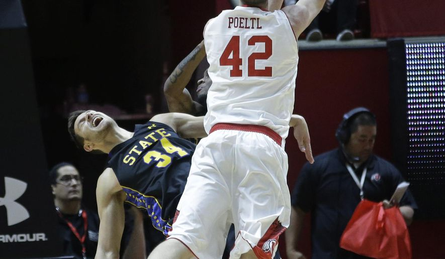 South Dakota State forward Cody Larson (34) falls as Utah forward Jakob Poeltl (42) shoots in the first half during an NCAA college basketball game Tuesday, Dec. 23, 2014, in Salt Lake City. (AP Photo/Rick Bowmer)