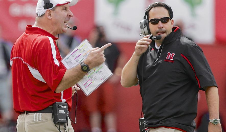 FILE - In this Sept. 14, 2013, file photo, Nebraska head coach Bo Pelini, left, calls instructions, with defensive coordinator John Papuchis looking on, duriing the first half of an NCAA college football game against UCLA in Lincoln, Neb. Papuchis is excited for the opportunity to fly solo in his last game as Nebraska's defensive coordinator. The firing of head coach Bo Pelini has left Papuchis in charge of every aspect of the Cornhuskers' defense in Saturday night's Holiday Bowl. (AP Photo/Nati Harnik, File)