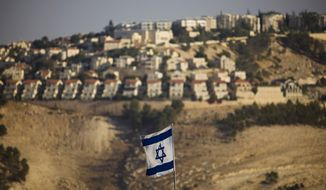 In this Monday, Sept. 7, 2009, file photo, an Israeli flag is seen in front of the West Bank Jewish settlement of Maaleh Adumim on the outskirts of Jerusalem. (AP Photo/Bernat Armangue, File)
