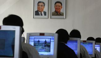 In this Thursday, Sept. 20, 2012, file photo, North Korean students use computers in a classroom with portraits of the country's later leaders Kim Il-sung, left, and his son Kim Jong-il hanging on the wall at the Kim Chaek University of Technology in Pyongyang, North Korea. Key North Korean websites were back online Tuesday, Dec. 23, 2014 after an hours-long shutdown that followed a U.S. vow to respond to a cyberattack on Sony Pictures that Washington blames on Pyongyang. (AP Photo/Vincent Yu, File)