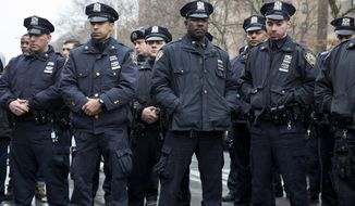 NYPD officers stand for a moment of silence at approximately 2:47 p.m., Tuesday, Dec. 23, 2014, near the site where New York Police Department officers Rafael Ramos and Wenjian Liu were murdered in the Brooklyn borough of New York at 2:47 this past Saturday. Police say Ismaaiyl Brinsley ambushed the two officers in their patrol car in broad daylight Saturday, fatally shooting them before killing himself inside a subway station. (AP Photo/Craig Ruttle) ** FILE **