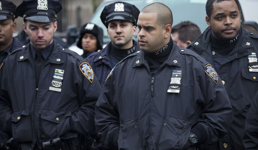 NYPD officers and others stand for a moment of silence at approximately 2:47, Tuesday, Dec. 23, 2014, near the site where New York Police Department officers Rafael Ramos and Wenjian Liu were murdered in the Brooklyn borough of New York at 2:47 this past Saturday. Police say Ismaaiyl Brinsley ambushed the two officers in their patrol car in broad daylight Saturday, fatally shooting them before killing himself inside a subway station. (AP Photo/Craig Ruttle)