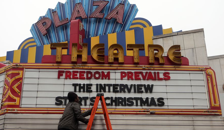 """Brandon Delaney, general manager of the Plaza Theatre, in Atlanta, Ga., finishes hanging the marquis Tuesday, Dec. 23, 2014 to announce that the theatre will be showing """"The Interview.""""  """"The Interview"""" was put back into theaters Tuesday when Sony Pictures Entertainment announced a limited Christmas Day theatrical release for the comedy that provoked an international incident with North Korea and outrage over its cancelled release. (AP Photo/Atlanta Journal-Constitution, Ben Gray)"""