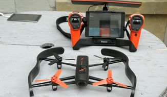 A Parrot Bebop drone (foreground) and the Skycontroller are among the many remotely controlled flying devices that have emerged as popular gifts this year. (Associated Press)