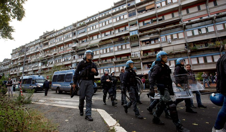 Italian riot police officers patrol a street as they protect a refugee center in Rome's outskirts in November. The working-class neighborhood of Tor Sapienza has seen several nights of clashes by residents blaming foreigners for crimes. (Associated Press)
