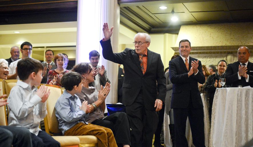 """In this Dec. 16, 2014 photo, Franz """"Swiss"""" Imfeld acknowledges applause during his retirement party in Grand Rapids, Mich. Swiss, as he is fondly known among his colleagues, launched his culinary career as head chef of the Pantlind Hotel 57 years ago and was appointed executive sous chef of the Amway Grand Plaza Hotel when it opened in 1981. The 83-year-old has managed the food purchasing department for the past 26 years. (AP Photo/Grand Rapids Press, Emily Rose Bennett) (Emily Rose Bennett 